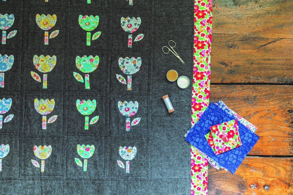 A quilt made with Liberty fabrics in progress, colourful fussy cut flowers on a dark background.